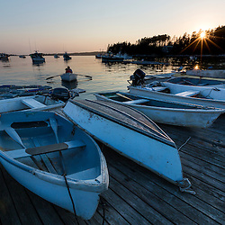 A fisherman rows his skiff in at sunset at the Spuce Head Fisherman's Co-op in South Thomaston, Maine.
