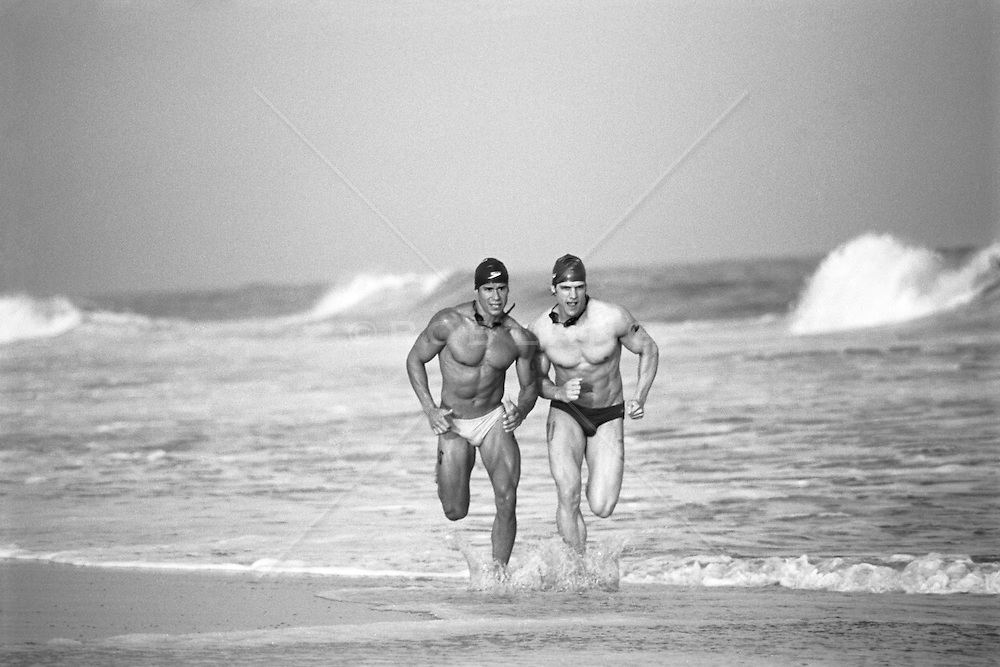 two athletic men in speedos running on the beach