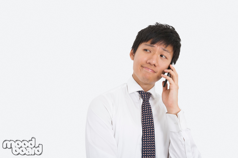 Thoughtful businessman using cell phone over white background