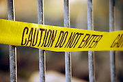 yellow tape with text Caution do not enter on metal barricade fence