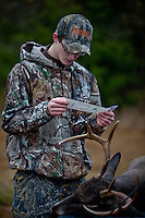 HUNTER WITH HIS FIRST BUCK AND HIS HUNTING LICENSE