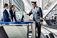Portrait of mature pilot talking with the airport staffs in boarding gate