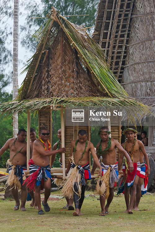 Yapese men in traditional clothing carrying a minature men's house at Yap Day Festival, Yap Island, Federated States of Micronesia