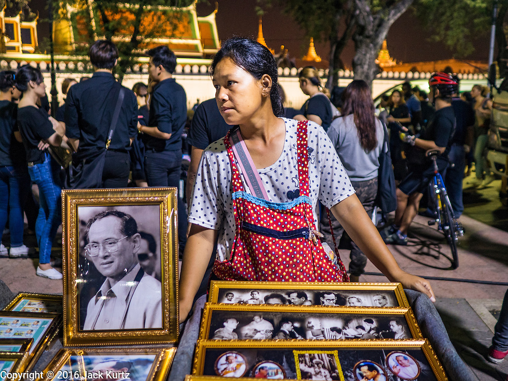 17 OCTOBER 2016 - BANGKOK, THAILAND:   A woman sells portraits of Bhumibol Adulyadej, the late King of Thailand, from a cart on Sanam Luang in central Bangkok. Thai King Bhumibol Adulyadej died Oct. 13, 2016. He was 88. His death comes after a period of failing health. Bhumibol Adulyadej, was born in Cambridge, MA, on 5 December 1927. He was the ninth monarch of Thailand from the Chakri Dynasty and is also known as Rama IX. He became King on June 9, 1946 and served as King of Thailand for 70 years, 126 days. He was, at the time of his death, the world's longest-serving head of state and the longest-reigning monarch in Thai history.      PHOTO BY JACK KURTZ