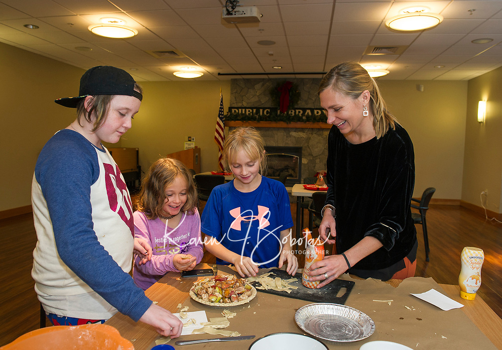 Addy, Delanie and Renee put a lattice top on their apple pie after a dollop of caramel sauce with Abi Maxwell at the Gilford Library pie making hour Tuesday afternoon.  (Karen Bobotas/for the Laconia Daily Sun)