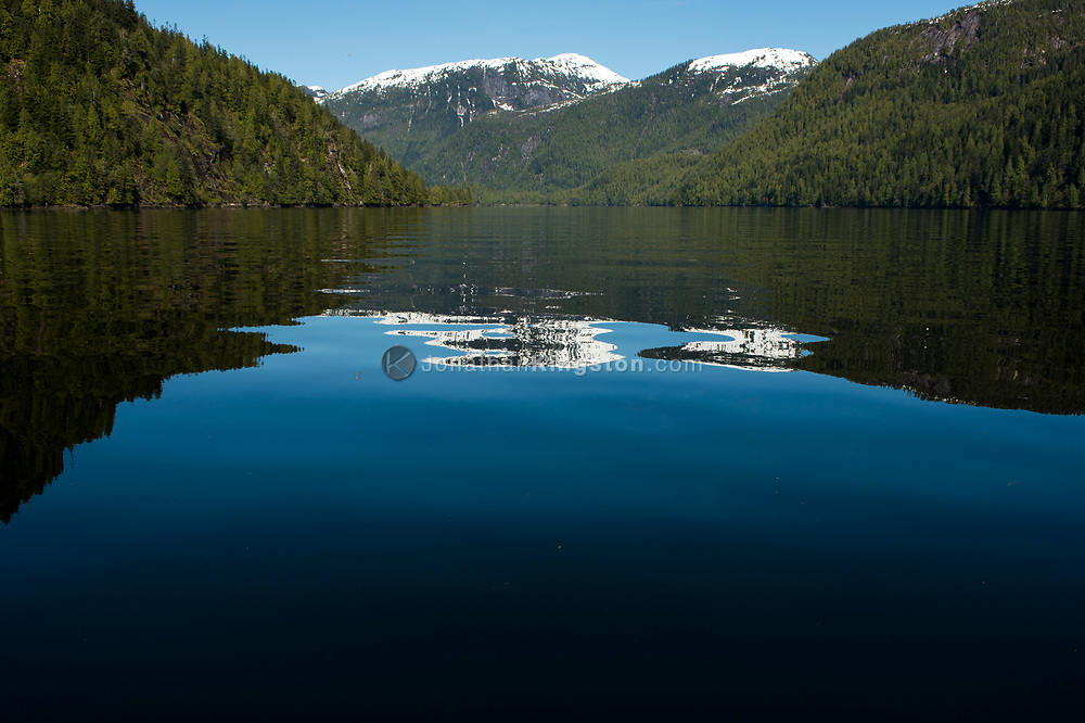 Reflections of snow capped mountains on the calm water of an inlet.