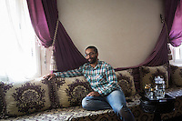 CASABLANCA, MOROCCO - 14 MAY 2016: Ahmed Abdul-Hakeem (28), the son of Luqman Abdul-Hakeem - a close follower of Malcolm X that chauffeured the African American activist around and introduced him to Cuban leader  Fidel Castro in September 1960 - listens to his father during an interview in his home in Sidi Maarouf, a district of Casablanca, Morocco, on May 14th 2016.<br /> <br /> Born in Cleveland, OH, in 1934, Luqman Abdul-Hakeem was raised in Flushing, Queens, and then moved to Bayside, where he graduated in 1952. He attended the New York Technical University for a few months before enrolling in the Navy, where he stayed for two years. Though he had asked for ship duty, he ended up in Springfield, Mass., and Glennclose, Ill. He moved to Brooklyn when his hitch was done and by 1966 was studying jujitsu and aikido. He met Malcolm X during one of his sermons on 116th street in Harlem, New York, in the late 50's. In 1985, Mr. Hakeem decided to move to Marocco because America wasn't a country where he wanted to raise hois children. He has been teaching aikido in the two dojos he owns in Casablanca until 2014, when he underwent a surgery.