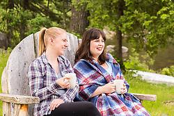 Two women drink coffee in a giant Adirondack chair outside the Appalachian Mountain Club's Gorman Chairback Lodge.