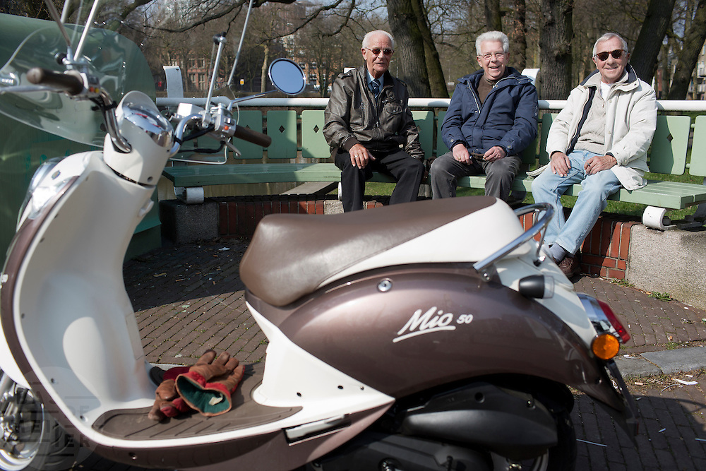 Drie bevriende mannen praten met elkaar op een bankje bij de Bartholemeusbrug in Utrecht.<br /> <br /> Three befriended elder men are enjoying the spring on a bench in Utrecht.