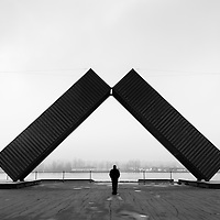 Solitary silhouetted figure standing under a giant art piece.