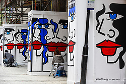 "© Licensed to London News Pictures. 04/08/2020. LONDON, UK.  Artist Anna Laurini (R) and her assistant work on her new artwork ""Urban Spinxes"".  Located outside a construction site just off Carnaby Street, the piece is  inspired by Pablo Picasso and Henri Matisse.  The construction company commissioned the artist to design something to cover up what would otherwise be bare wooden hoardings.  Photo credit: Stephen Chung/LNP"