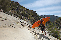 Female kayaker walking on rock, side view