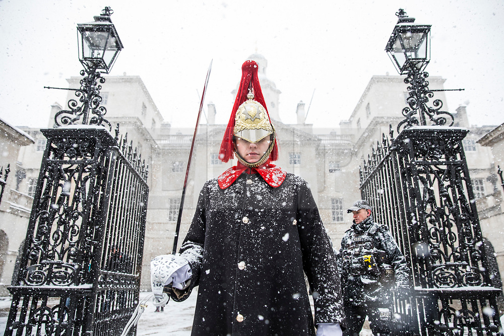 © Licensed to London News Pictures. 28/02/2018. London, UK. A member of the Household Cavalry Guard braves heavy snow on Whitehall. Severe weather is set to continue as the 'Beast from the East' brings freezing Siberian air to the UK. Photo credit: Rob Pinney/LNP