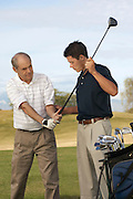 Young Man Helping Man with His Grip on Golf Club
