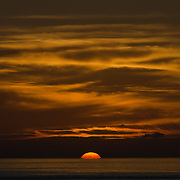 A beautiful golden sunset just before the sun disappeares below the horizon. The light clouds above catch the sun's last rays of the day. Taken at Swains Reef on the southern end of the Great Barrier Reef of the coast of Queensland, Australia.