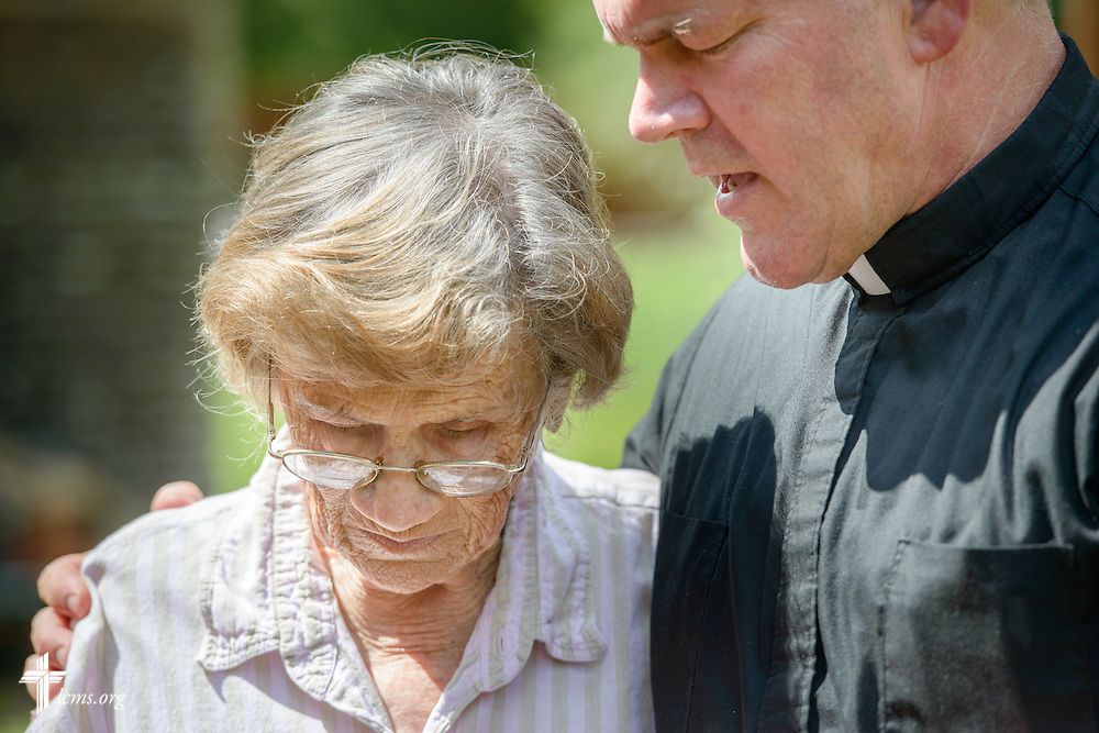 The Rev. David Buss, senior pastor of Trinity Lutheran Church, Baton Rouge, La., prays with charter member Althea Neptune and the Rev. Ross Johnson (not pictured), director of LCMS Disaster Response, outside her flood-damaged home on Wednesday, Sept. 14, 2016, in Baton Rouge. LCMS Communications/Erik M. Lunsford