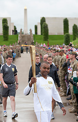© Licensed to London News Pictures. 30/06/2012. National Memorial Arboretum, Staffordshire, UK. The Olympic Torch Relay visited the National Memorial Arboretum in Staffordshire earlier today. Cpl Johnson Beharry VC carried the Olympic Torch along the causeway, climbed the steps and paused at the Armed Forces Memorial to remember the fallen. Photo credit : Dave Warren/LNP