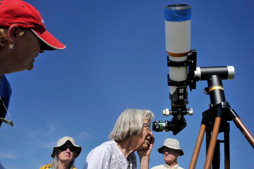 """mkb060512a/metro/Marla Brose/060512.Fran Fosnaugh looks through Amy Estelle's telescope to see the transit of venus, at the Anderson Abruzzo Albuquerque International Balloon Museum, Tuesday, June 5, 2012, in Albuquerque, N.M. """"It looked like a red dot on a green ball,"""" Fosnaugh said. She attributed the colors to either the telescope or her glasses. (Marla Brose/Albuquerque Journal)"""