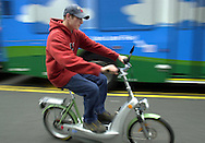 PHILADELPHIA - MAY 13:  A young man test rides a battery powered Egovehicle bicycle during the Tour de Sol: Great American Green Transportation Festival May 13, 2003 in Philadelphia, Pennsylvania. The tour is a series of festivals linked by a road rally championship for advanced vehicles. Anyone can compete with a road worthy hybrid vehicle, alternative fueled, fuel cell, or solar assisted electric sedan, truck, bus, or motorcycle built by manufacturers, students, or visionaries. The event is being held during National Transportation Week, and Clean Air Month. (Photo by William Thomas Cain/Getty Images)