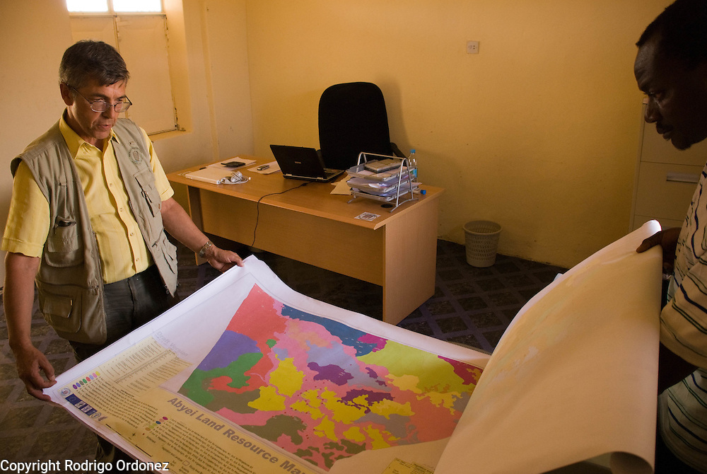 Mercy Corps' Program Manager JJ Franc de Ferrière (left) and Livelihoods Manager Augustino Sowa show the map of land resources of the Abyei area, produced by their program.