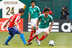 March 26, 2011; Oakland, CA, USA;  Mexico midfielder Antonio Naelson Sinha (17) dribbles the ball past Paraguay forward Edgar Benitez (10) during the first half at Oakland-Alameda County Coliseum. Mexico defeated Paraguay 3-1.