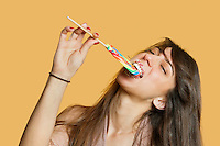 Portrait of a young woman eating lollipop over colored background