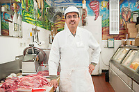 Portrait of a butcher wearing apron standing near meat in store