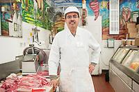 Portrait of a butcher wearing apron standing near meat in store