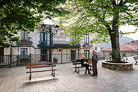 """PISCIOTTA, ITALY - 22 APRIL 2018: Two elderly men are seen here in the main square in Pisciotta, Italy, on April 22nd 2018.<br /> <br /> Former restaurant owners Donatella Marino and her husband Vittorio Rimbaldo have spent the recent years preparing and selling salted anchovies, called alici di menaica, to a growing market thanks to a boost in visibility from the non-profit Slow Food.  The ancient Menaica technique is named after the nets they use brought by the Greeks wherever they settled in the Mediterranean. Their process epitomizes the concept of slow food, and involves a nightly excursion with the special, loose nets that are built to catch only the larger swimmers. The fresh, red anchovies are immediately cleaned and brined seaside, then placed in terracotta pots in between layers of salt, to rest for three months before they're aged to perfection.While modern law requires them to use PVC containers for preserving, the government recently granted them permission to use up to 10 chestnut wood barrels for salting in the traditional manner. The barrels are """"washed"""" in the sea for 2-3 days before they're packed with anchovies and sea salt and set aside to cure for 90 days. The alici are then sold in round terracotta containers, evoking the traditional vessels that families once used to preserve their personal supply.<br /> <br /> Unlike conventional nets with holes of about one centimeter, the menaica, with holes of about one and half centimeters, lets smaller anchovies easily swim through. The point may be to concentrate on bigger specimens, but the net also prevents overfishing."""