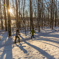 Two women snowshoeing while the sun shines through the forest above Indian Hill Reservoir in West Newbury, Massachusetts.