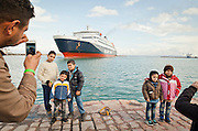 Greece, Chios<br /> <br /> At the harbor in Chios, while waiting for the ferryboat parents take images of their children in front of an incoming ferryboat. <br /> <br /> January 4th, 2016 refugees from Afghanistan, Iran, Syria and other countries form the near east, made it to Greece by crossing the Aegean sea with rubber boats. <br /> After their registration on the Greek island, the wait for the cruise to Athens with Greek ferryboat.<br /> <br /> <br /> <br /> keine Veroeffentlichung unter 50 Euro*** Bitte auf moegliche weitere Vermerke achten***Maximale Online-Nutzungsdauer: 12 Monate !!