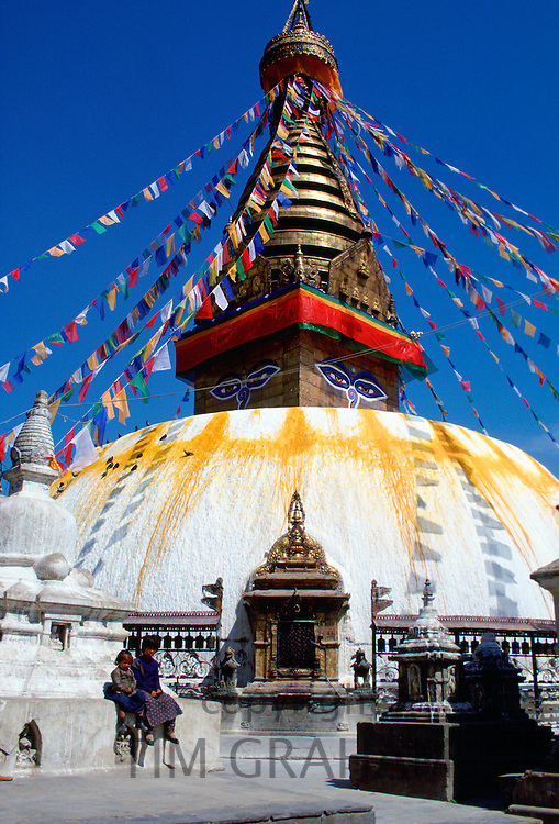 Children by the flag-bedecked sacred monument Swayambhunath Stupa in Kathmandu valley in Nepal