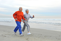 Senior couple jogging on the beach in the early morning