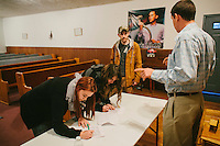 LaFollette, TN - Nov. 14, 2013: Andrew Hamblin, right, pastor of the Tabernacle Church of God, talks with Emily Craig, left to right, Summer Breeding, and Daniel Riggs as they sign a petition supporting the church's right to handle serpents. The church, whose congregation regularly handles snakes as part of services, had their snakes confiscated in early November by the Tennessee Wildlife Resources Agency for violating a Tennessee law against handling serpents in church. <br /> <br /> Photo by Shawn Poynter