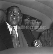 Rome, Termini Station, 03-10-1952. Jazz musicians Louis Armstrong, just arrived in town by train, sitting in a car surrounded by fans  / Roma, Stazione Termini, 03-10-1952. Il musicista jazz Louis Armstrong, appena arrivato in treno, seduto in un'automobile circondata dai fans  - Marcello Mencarini Historical Archives