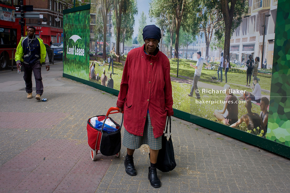 Elderly, frail lady struggles with shopping past a regeneration project hoarding image at Elephant & Castle, London borough of Southwark.