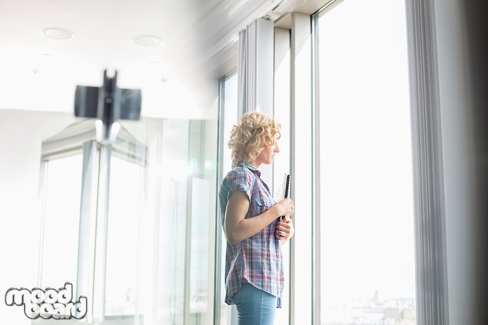 Side view of creative businesswoman holding files while looking through window in office
