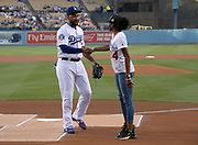 Jun 13, 2018; Los Angeles, CA, USA; Kendall Ellis (4) shakes hands with Los Angeles Dodgers center fielder Matt Kemp during a ceremonial relay before a MLB game against the Texas Rangers at Dodger Stadium. Ellis ran the anchor leg on the Southern California Trojans women's 4 x 400m relay that won the NCAA title in the final even to win  the national team title.