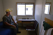 Nick from Minnesota works 15days on with 6 days off on a Sanjel fracking crew this is his room.<br /> <br /> ATCO workers lodge, more commonly known as a &quot;mancamp&quot; just north of Williston. The camps are constructed from prefabricated containers, and offer small clean functional rooms and good cafeteria food.<br /> <br /> Most workers here are employed by an oil services company and spend two weeks onsite, working15 hour days. they then get a week off to see their family. The pay makes it worthwhile as it is often double what they could get otherwise employed in the their professions.<br /> <br /> North Dakota oil boom. Based around the town of Williston, hydraulic fracturing, also known as 'fracking' has enabled a vast reserve of previously unobtainable oil to be accessed.