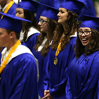A Tupelo High School graduating senior smiles at family members after entering the BancorpSouth Arena for the Tupelo High graduation ceremony Friday night.