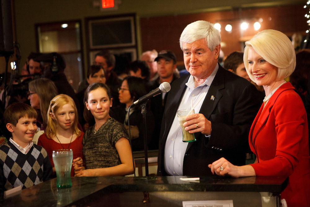 Republican presidential candidate Newt Gingrich tries a root beer float his wife made while his grandchildren, left and wife Callista Gingrich, right watch as they campaign at the Adams Street Espresso Shop on Friday, December 30, 2011 in Creston, Iowa.