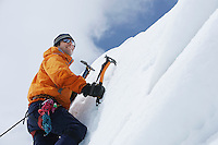 Mountain climber going up snow with axes