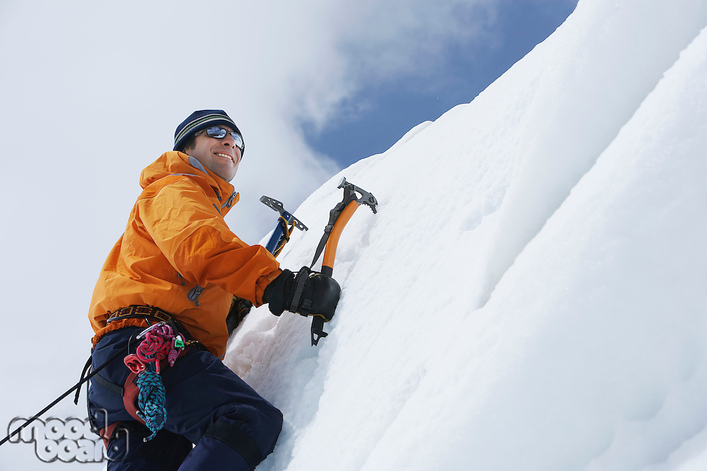 Mountain climber going up snow with axes