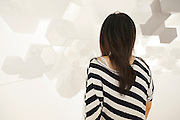 TOKYO, JAPAN, 4 MAY -  Woman wearing black and white stripe is standing in front of a polygonal structure - Architecture exhibition in a  museum in Otemachi - May 2010