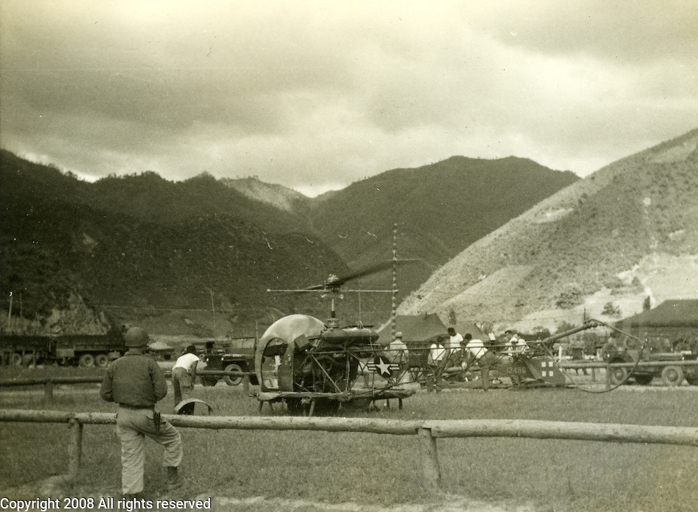 "A black and white photograph taken during the Korean War shows an OH-13 Sioux helicopter. The photo is marked, ""evacuation by helicopter. land mine casualty 1952 - flight to Chunchon."""