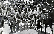 Turkish infantry, rifles on their shoulders, on the march led by a mounted officer, c1914.