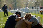 ARLINGTON, VA - NOVEMBER 11: Chuck Jackson (L) and Kimberly Shrauger (R) comfort Kimberly's husband Lowell Shrauger as he visits the grave of his life-long friend, Staff Sgt. Jamie L. Huggins, on Veteran's Day at Arlington National Cemetery on November 11, 2012 in Arlington, Virginia.