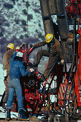 Stock photo of oilfield workers setting up secondary recovery operations onsite in Utah.
