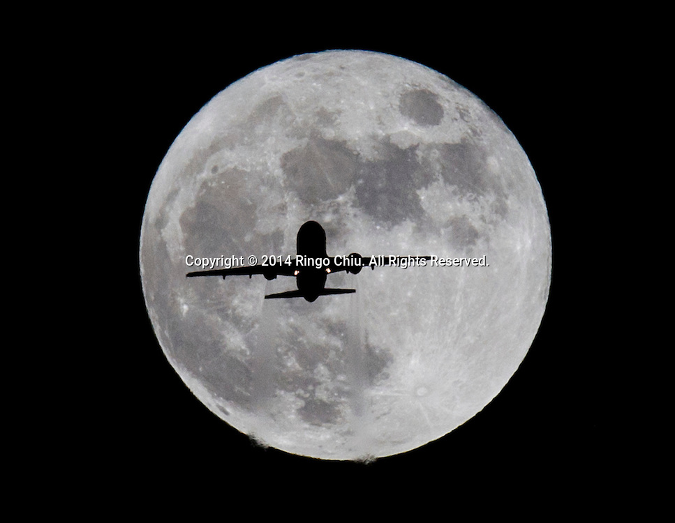 An airplane approaches Los Angeles International Airport and flies past the full moon on Thursday, November 6, 2014 in Los Angeles, California.(Photo by Ringo Chiu/PHOTOFORMULA.com)