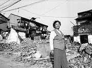 Shanghai Portraits 7 - A woman walks through the rubble of an old neighborhood that is being demolished to make room for modern buildings.